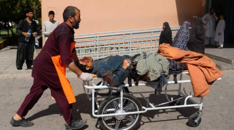 A humanitarian official transports wounded Afghan civilian from site of Bus bombing on the Kandahar-Herat Highway. Image Source: Al Jazeera